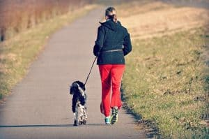 woman walking with dog to reduce stress